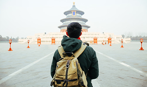 A Chinese student with a backpack walking in Beijing