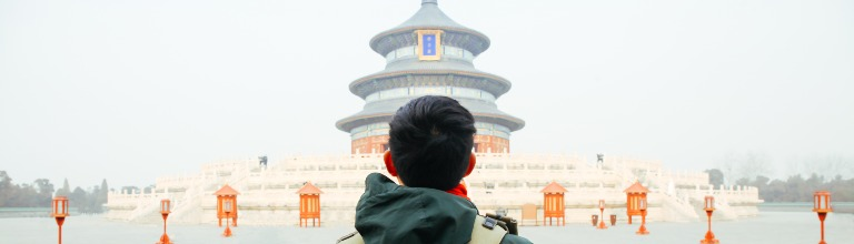 A young traveller walking towards the temple of heaven in Beijing, China.